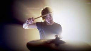 Drummer hitting bell of ride cymbal