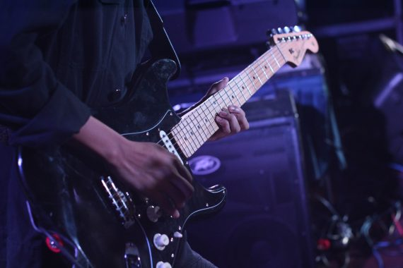 close up of electric guitarist performing