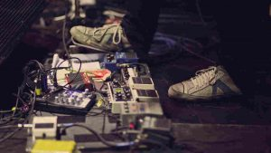 guitarist stepping on guitar effects pedals