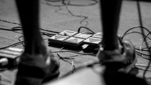 female guitar player using guitar effects pedals