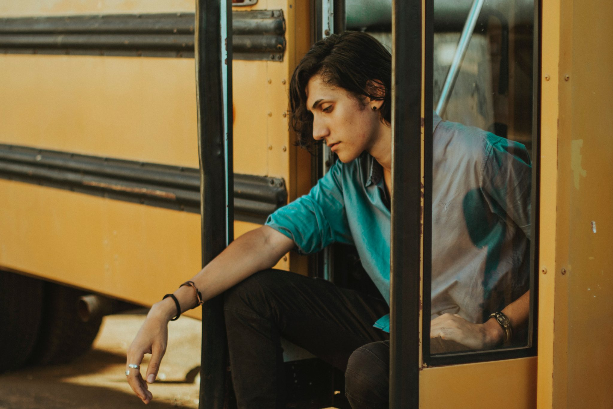 man sitting on the steps of a school bus