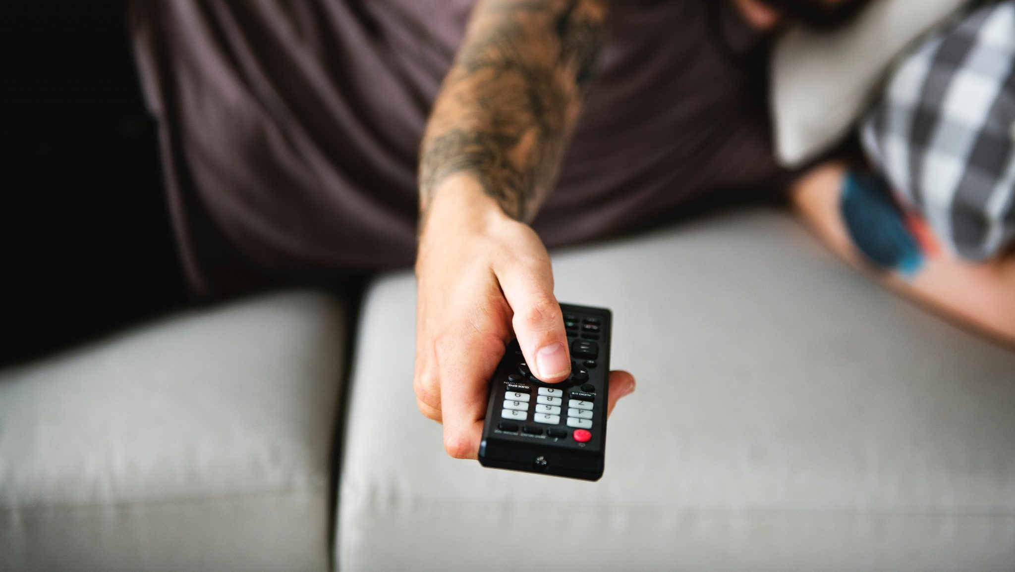 man with tattooed arm laying on a couch and using a remote control