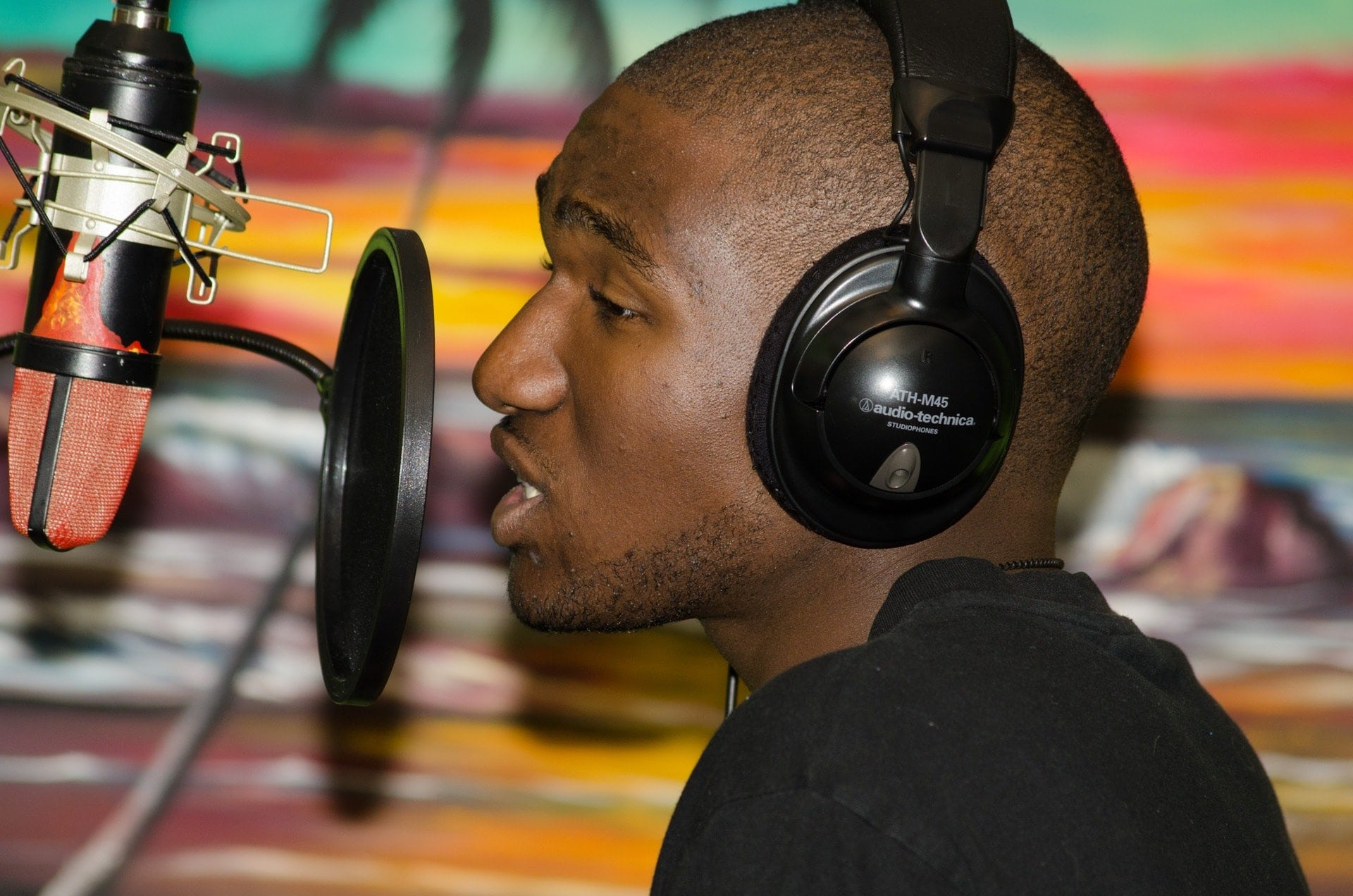 male singer recording with headphones