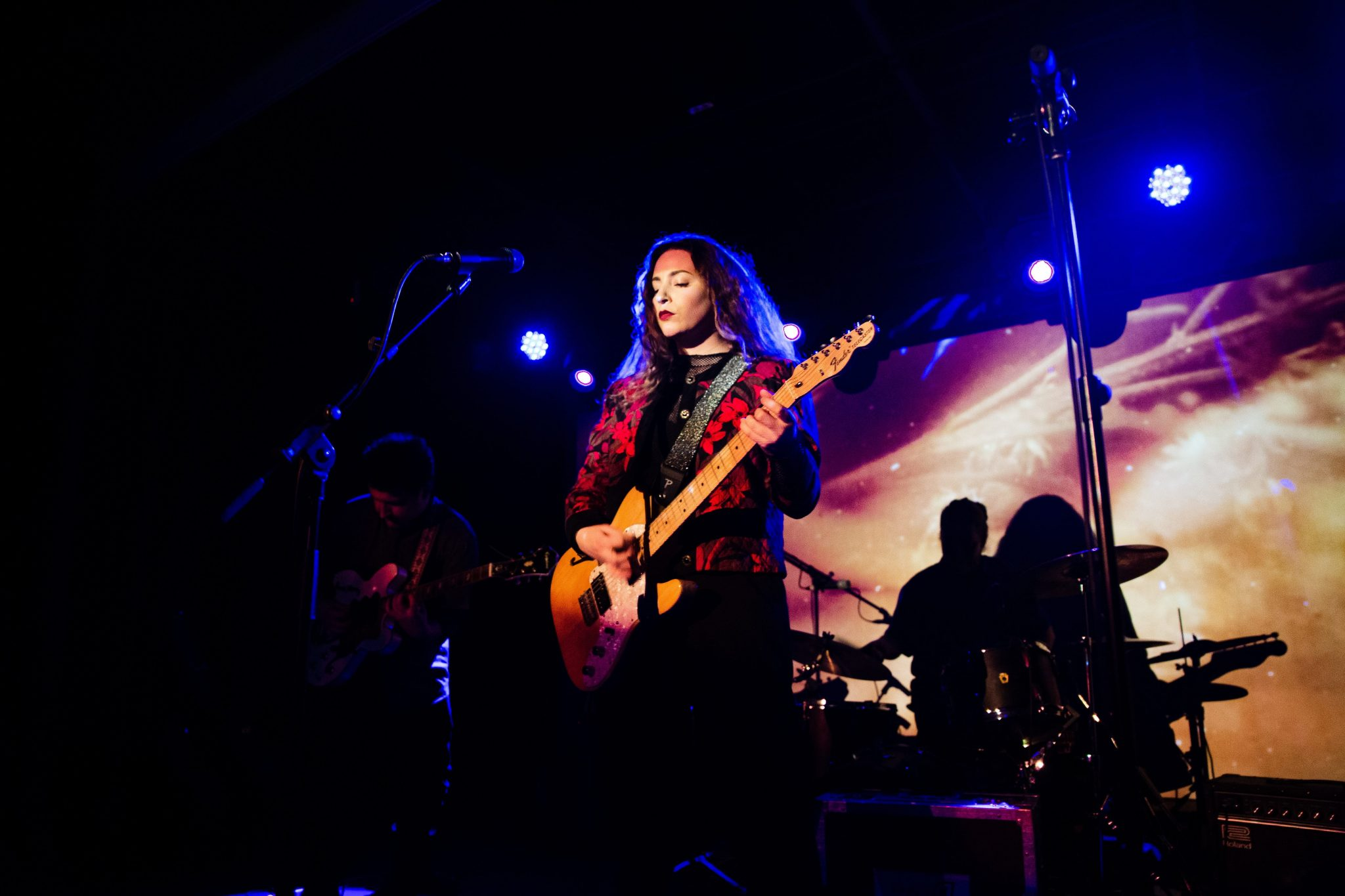 female musician singing and playing guitar in front of an audience