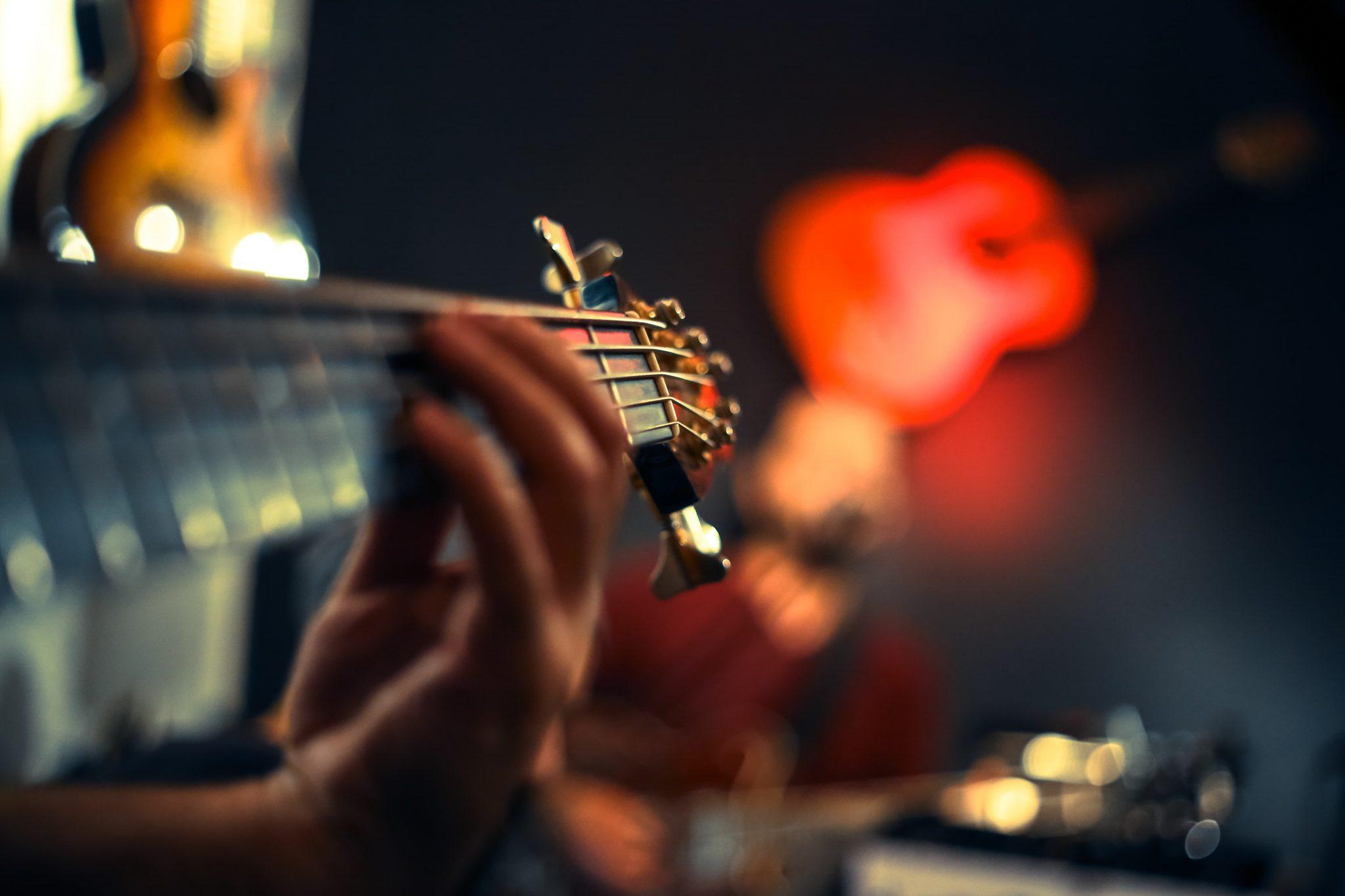guitarist's fretting hand on guitar fretboard