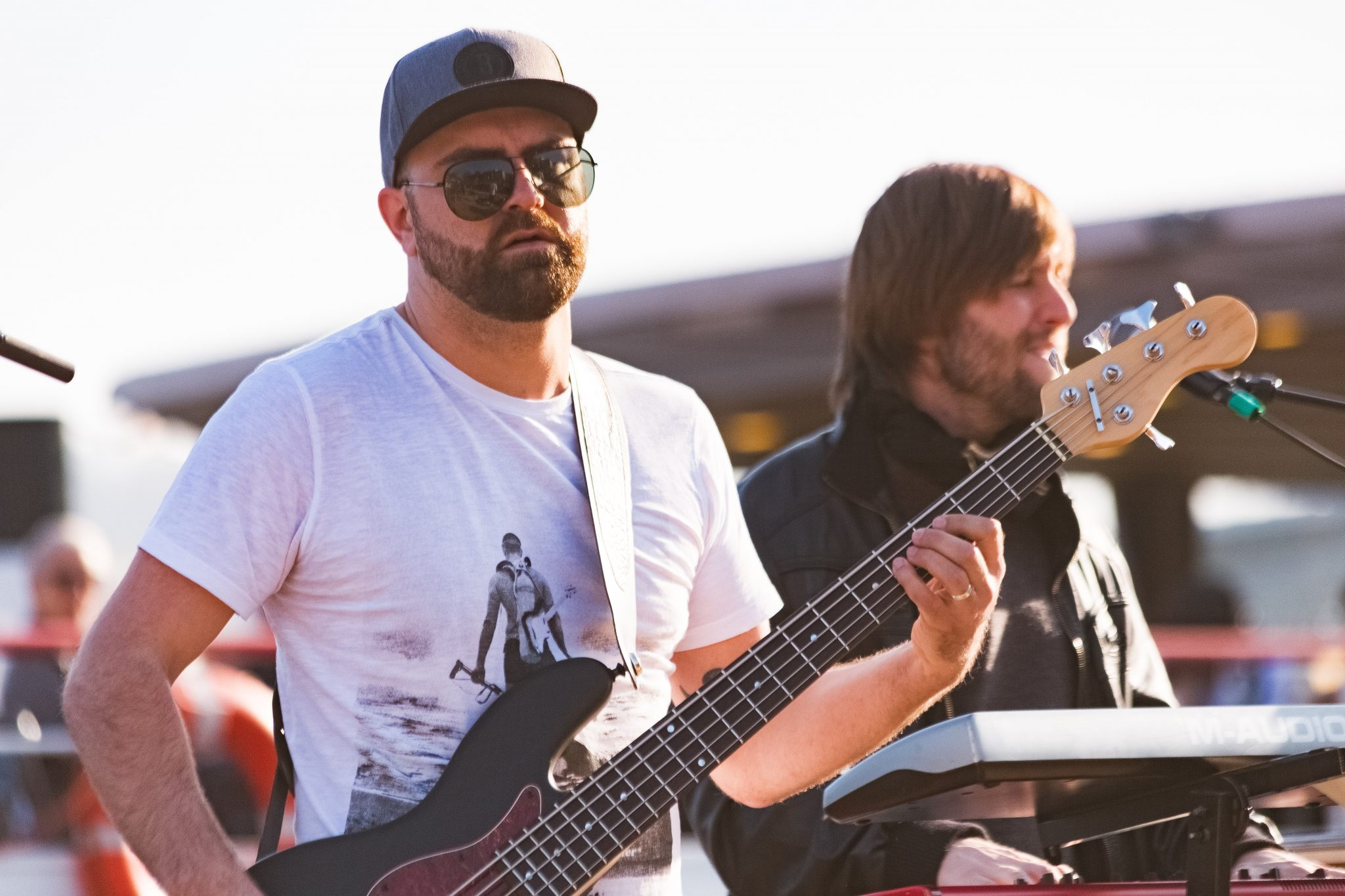 bassist and keyboardist performing on outdoor stage
