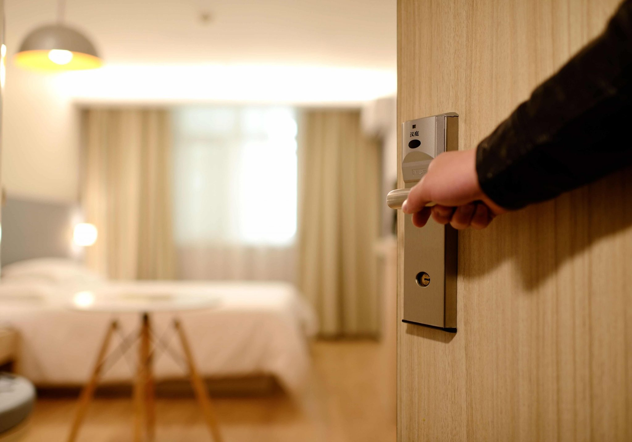 person opening hotel room door