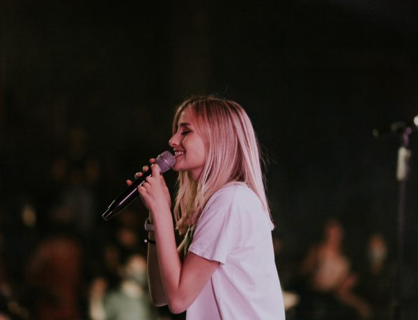 woman singing on stage in front of large crowd