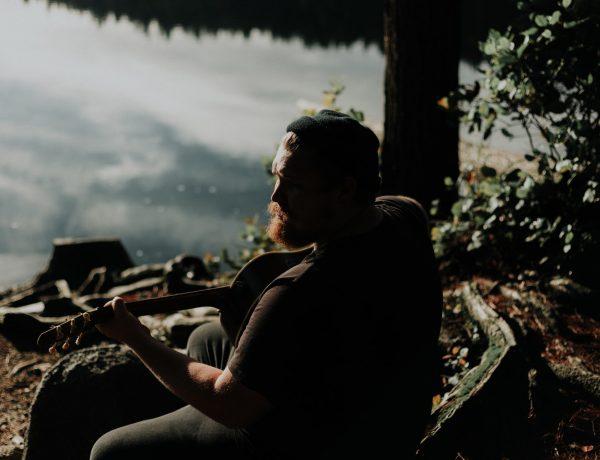man playing guitar by the lake